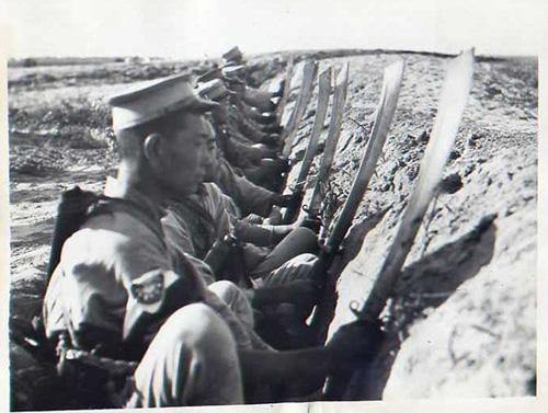 Ancora i soldati cinesi, in trincea, con i dadao sguainati e il fodero chiaramente visibile dietro le loro spalle.